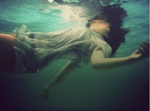 only her face remains above water