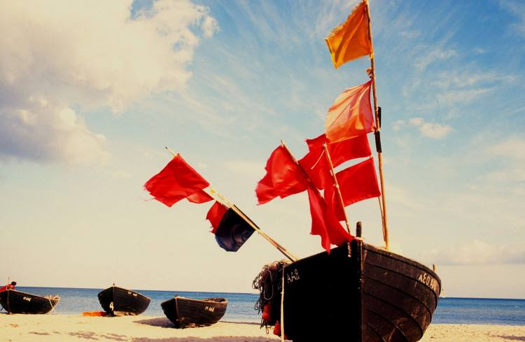 row boat with red flags on stranded island