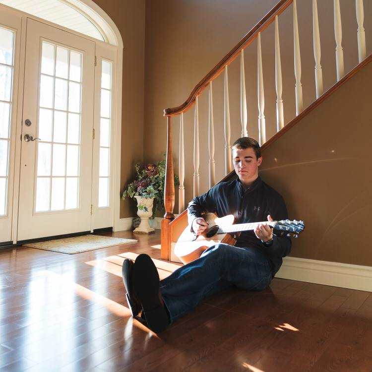 Man playing guitar alone at home