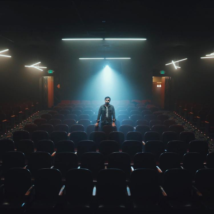Man alone in auditorium with spotlight shining down onto him