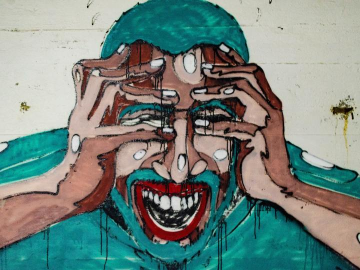 street art of a man his hands to his face, screaming