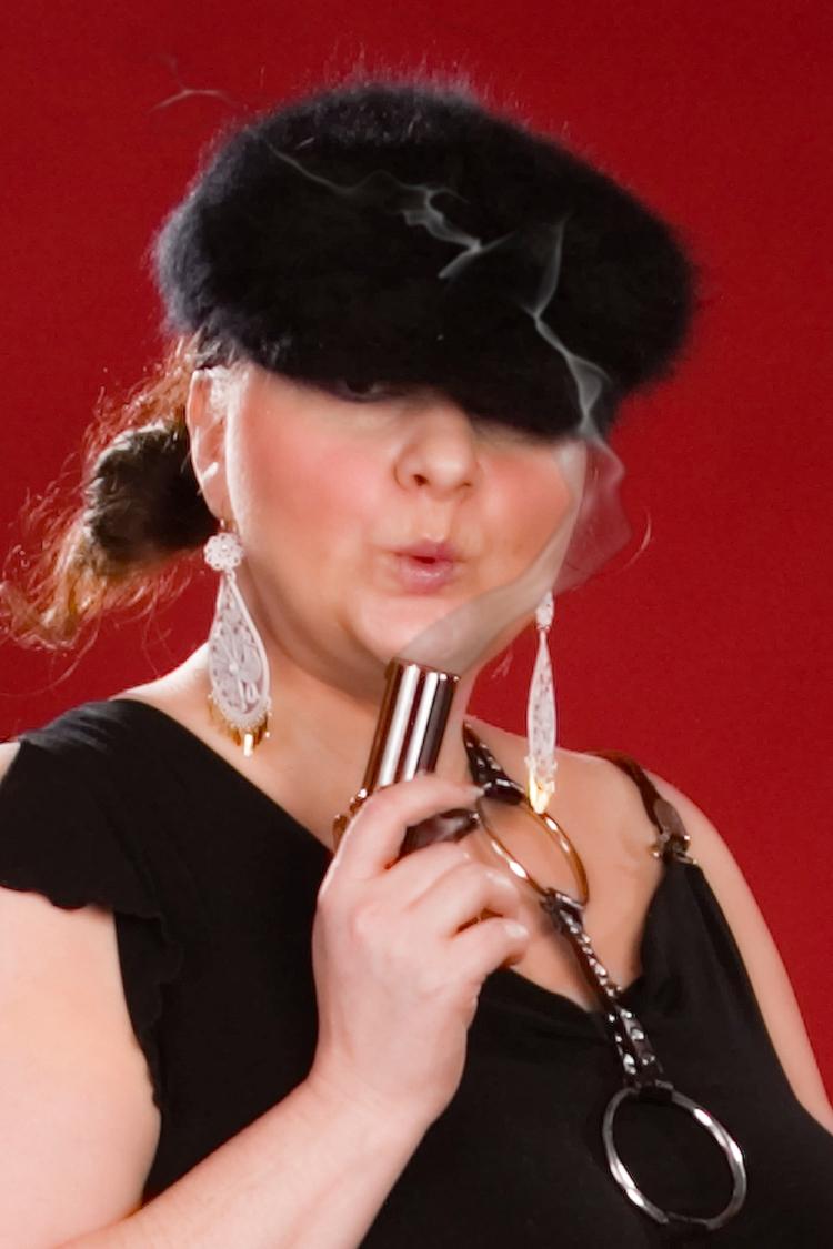 female hoodlum holding a smoking gun